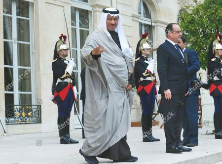 Kuwait's Prime Minister Sheikh Jaber Al-Mubarak Al-Hamad Al-Sabah, left, waves as he leaves the Elysee Palace in Paris, France, after his meeting with French President Francois Hollande, right