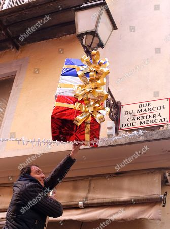 Jean Pierre Lellouche hangs a decoration in the colors of France, above his shop in Nice, southeastern France, . French President Francois Hollande called on his compatriots to hang French tricolor flags on Friday to pay homage to the victims of the Nov. 13, attacks, an unusual appeal by a Socialist leader in a country where flag-waving is often associated with nationalists and the far right