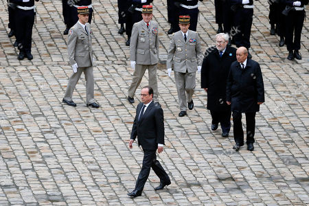 French President Francois Hollande, followed by, from top left, French army general Bruno Le Ray, military governor of Paris, French President Hollande's Military Chief of Staff General Benoit Puga, French Army Chief of Staff, General Pierre de Villiers, French Junior Minister for Veterans and Remembrance, Jean-Marc Todeschini, and French defense minister Jean Yves Le Drian, attend a Military ceremony at the Military Hotel National des Invalides, in Paris, France, . With France still reeling from last week's deadly attacks in Paris, Prime Minister Manuel Valls warned Thursday that Islamic extremists might at some point use chemical or biological weapons, and urged lawmakers to extend a national state of emergency by three months
