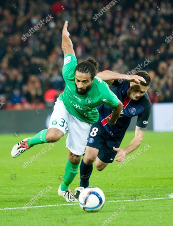 Stock Photo of Saint Etienne's Benoit Assou-Ekotto left, challenges for the ball with PSG's Thiago Motta during their French League One soccer match in Parc des princes stadium, in Paris, France