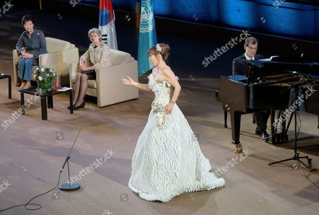 South Korea's artist Sumi Jo performs on stage while South Korea President Park Geun-hye, left, and UNESCO Director General Irina Bokova, 2nd left, look on as part of the organization's 70th anniversary at it headquarters in Paris, France, Tuesday Dec, 1, 2015. President Park signed an agreement for the creation of an International Centre of Martial Arts for Youth Development and Engagement under the auspices of UNESCO in the city of Chungju