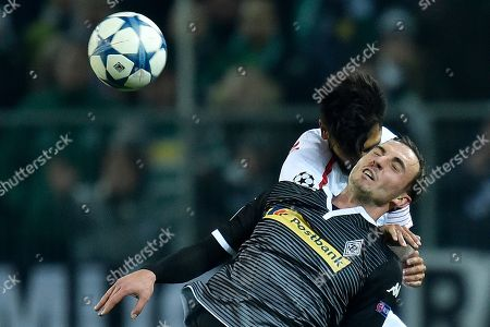 Sevilla's Benoit Tremoulinas, back, challenges Moenchengladbach's Josip Drmic, front, during the Champions League Group D soccer match between Borussia Moenchengladbach and FC Sevilla in Moenchengladbach, western Germany
