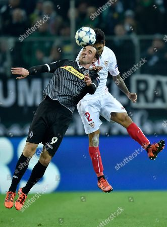 Sevilla's Benoit Tremoulinas, right, challenges Moenchengladbach's Josip Drmic, left, during the Champions League Group D soccer match between Borussia Moenchengladbach and FC Sevilla in Moenchengladbach, western Germany