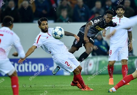 Moenchengladbach's Ibrahima Traore, right, shoots a ball past Sevilla's Benoit Tremoulinas, left, during the Champions League Group D soccer match between Borussia Moenchengladbach and FC Sevilla in Moenchengladbach, western Germany