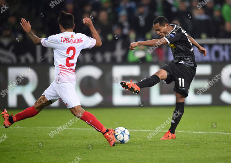 Sevilla's Benoit Tremoulinas, left, blocks a shot by Moenchengladbach's Raffael during the Champions League Group D soccer match between Borussia Moenchengladbach and FC Sevilla in Moenchengladbach, western Germany