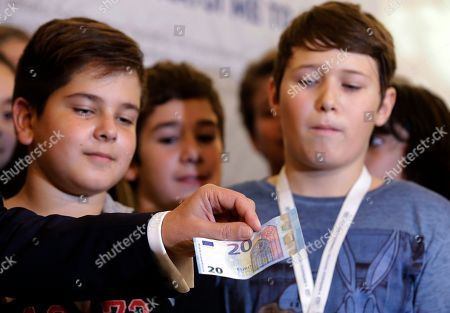 Pupils look the new 20 euro note as Yannis Stournaras governor of Bank of Greece presents it in Athens, . The new 20 euro notes will circulate in the 19 Eurozone countries on Wednesday. Greece was formally cleared Monday to get the next batch of bailout loans due from its third financial rescue after the cash-strapped country implemented a series of economic reform measures that European creditors had demanded