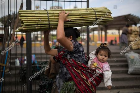 A woman balances a bundle of bamboo canes on her head as she leaves the Central Market in Guatemala City, . A TV comic and a former first lady will vie for Guatemala's presidency Sunday. The country will have either its first female president or its first political neophyte in the office. The victor will have to respond quickly to demands for deep reform, said Alejandro Maldonado, who took over as interim president after Otto Perez Molina swapped the presidential palace for a prison cell Sept. 3