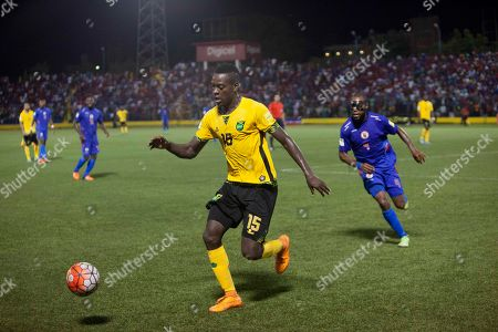 Jamaica's Je-Vaughn Watson, center, controls the ball against Haiti's Kim Jaggy during a 2018 World Cup qualifying soccer match, in Port-au-Prince, Haiti