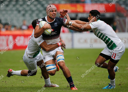 Stock Picture of Hong Kong's Christopher Russell Maize, center, is tackled by Iran's Omid Zarei, right, at the Asia Rugby Sevens qualifier in Hong Kong