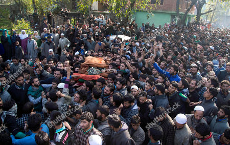 Kashmiri villagers carry the body of Adil Hussain Khandey, a local militant of Hizbul Mujahideen, during his funeral procession in Barbuk village, some 60 Kilometers south of Srinagar, Indian controlled Kashmir, . Thousands of villagers shouted slogans as they participated in the funeral procession of two Hizbul Mujahideen militants who were killed in an overnight encounter with security forces in a southern village of the region