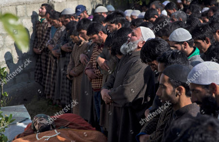 Kashmiri Muslim villagers pray by the body of Adil Hussain Khandey, a local militant of Hizbul Mujahideen, during his funeral procession in Barbuk village, some 60 Kilometers South of Srinagar, Indian controlled Kashmir, . Thousands of villagers shouted slogans as they participated in the funeral procession of two Hizbul Mujahideen militants who were killed in an overnight encounter with security forces in a southern village of the region