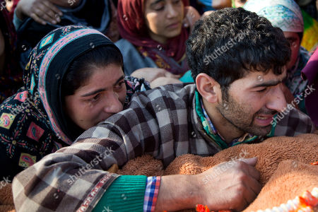Unidentified relatives grieve near the body of Adil Hussain Khandey, a local militant of Hizbul Mujahideen, during his funeral procession in Barbuk village, some 60 Kilometers south of Srinagar, Indian controlled Kashmir, . Thousands of villagers shouted slogans as they participated in the funeral procession of two Hizbul Mujahideen militants who were killed in an overnight encounter with security forces in a southern village of the region