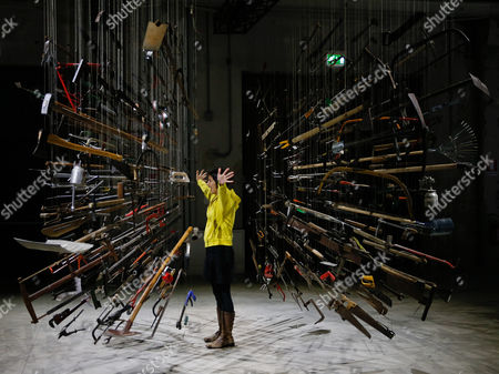 A girl poses for a picture into the installation 'Controller of the Universe' by artist Damian Ortega, part of the 'Casino' exhibition, at the Hangar Bicocca in Milan, Italy