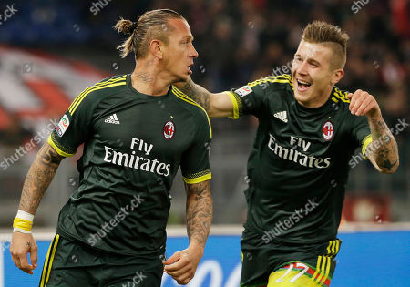 AC Milan's Philippe Mexes, left, celebrates with his teammate Juraj Kucka after scoring during a Serie A soccer match between Lazio and Milan, at Rome's Olympic Stadium