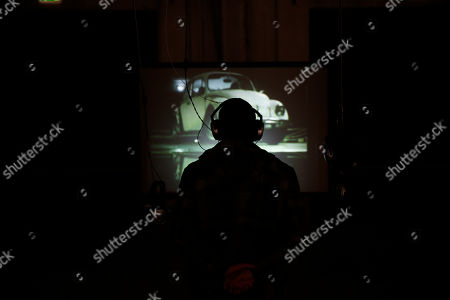 A visitor listens on a headphone and watches video installation by artist Damian Ortega part of the 'Casino' exhibition, at Hangar Bicocca in Milan, Italy