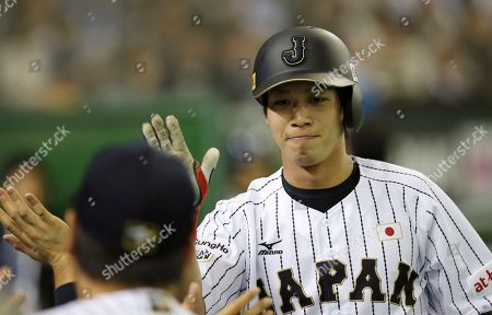 Stock Photo of Tetsuto Yamada Japan's Tetsuto Yamada celebrates with teammates after hitting a solo home-run off Mexico's starter Miguel Pena during the first inning of their third-place game at the Premier12 world baseball tournament at Tokyo Dome in Tokyo