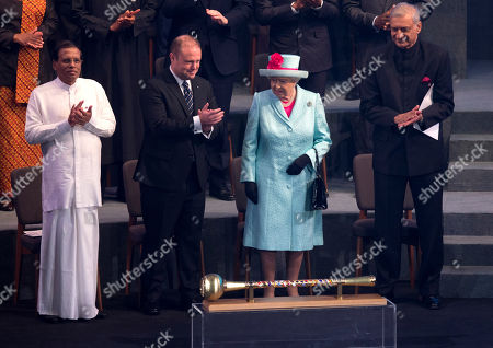 Britain Queen Elizabeth II is flanked from left, by President of Sri Lanka Maithripala Sirisena, outgoing Commonwealth Chair-in-Office, Malta's Prime Minister Joseph Muscat, and Commonwealth Secretary-General Kamalesh Sharma, as she attends the opening of the CHOGM