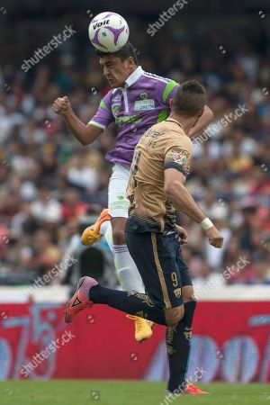 Stock Picture of Luis Venegas, Dante Lopez Jaguares' Luis Venegas, top, heads for the ball with Pumas' Dante Lopez during a Mexican soccer league match in Mexico City