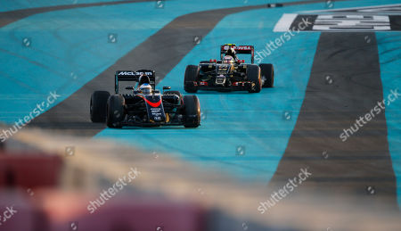 McLaren driver Fernando Alonso of Spain, leads Lotus driver Pastor Maldonado of Venezuela after crashing at the first lap during the Emirates Formula One Grand Prix at the Yas Marina racetrack in Abu Dhabi, United Arab Emirates