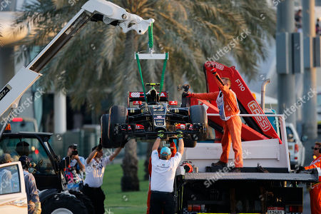 Lotus driver Pastor Maldonado of Venezuela's car is carried on a track from marshals after failing to complete the Emirates Formula One Grand Prix at the Yas Marina racetrack in Abu Dhabi, United Arab Emirates