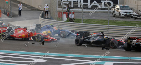 McLaren driver Fernando Alonso of Spain, second from right, crashes with Lotus driver Pastor Maldonado of Venezuela as Ferrari driver Sebastian Vettel of Germany, left, and Sauber driver Felipe Nasr of Brazil run during the Emirates Formula One Grand Prix at the Yas Marina racetrack in Abu Dhabi, United Arab Emirates