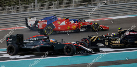 McLaren driver Fernando Alonso of Spain, left, crashes with Lotus driver Pastor Maldonado of Venezuela as Ferrari driver Sebastian Vettel of Germany, left, and Sauber driver Felipe Nasr of Brazil run during the Emirates Formula One Grand Prix at the Yas Marina racetrack in Abu Dhabi, United Arab Emirates