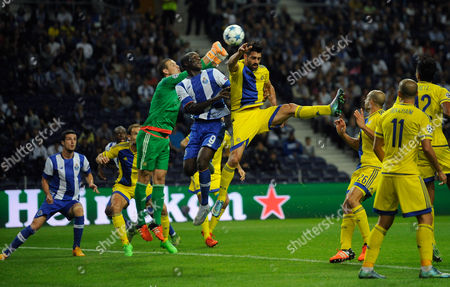 Porto's Vincent Aboubakar, center, jumps for the ball with Maccabi's goalkeeper Predrag Rajkovic, center left, and Omri Ben Harush during the Champions League group G soccer match between FC Porto and Maccabi Tel-Aviv FC at the Dragao stadium in Porto, Portugal