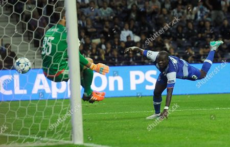 Porto's Vincent Aboubakar, right, scores the opening goal past Maccabi's goalkeeper Predrag Rajkovic, left, during the Champions League group G soccer match between FC Porto and Maccabi Tel-Aviv FC at the Dragao stadium in Porto, Portugal