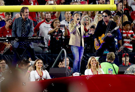 Arnel Pineda, Neal Schon, Jonathan Cain Singer Arnel Pineda, keyboardist Jonathan Cain and guitarist Neal Schon of Journey, perform the national anthem prior to an NFL football game between the Arizona Cardinals and the Baltimore Ravens, in Glendale, Ariz