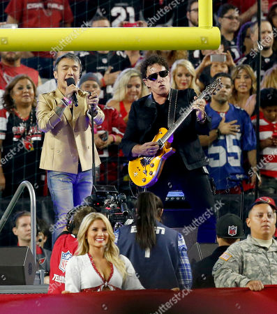 Arnel Pineda, Neal Schon Singer Arnel Pineda and guitarist Neal Schon of Journey, perform the national anthem prior to an NFL football game between the Arizona Cardinals and the Baltimore Ravens, in Glendale, Ariz