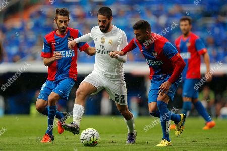 Real Madrid's Isco, center, duels for the ball with Levante's Jose Mari, left, during a Spanish La Liga soccer match between Real Madrid and Levante at the Santiago Bernabeu stadium in Madrid, Spain