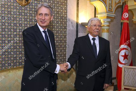 British Foreign Secretary Philip Hammond, left, shakes hands with his Tunisian counterpart Taieb Baccouche in Tunis, . Hammond has flown to Tunisia to discuss the terror attacks that hit the country this year. Britons were among the 38 people killed in Sousse. The mass shooting followed a strike in March, when militants killed 22 people at the Bardo museum in the capital Tunis