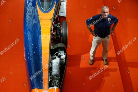Project director Richard Noble poses for a photograph as he stands next to the British backed Bloodhound SSC streamliner car, designed to reach speeds of 1000 miles per hour (1609 kilometers per hour), as it is displayed to the media prior to being show to members of the public, London, . The project aims to make high speed runs in South Africa in 2016, with a view to breaking the 1000 miles per hour (1609 kilometers per hour) in 2017. The car will use a Rolls-Royce EJ200 fighter jet engine and a Nammo rocket to achieve the required velocity