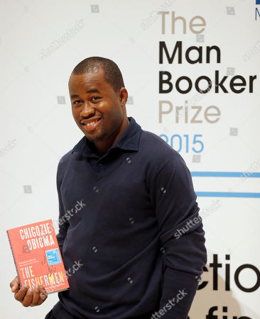 Author Chigozie Obioma poses with his book 'The Fishermen' on stage at the Royal Festival Hall in London, . Obioma is one of six shortlisted authors of the 2015 Man Booker Prize for Fiction, and the winner will be announced Tuesday Oct. 13