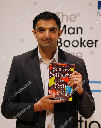 Author Sunjeev Sahota poses with his book 'The Year of The Runaways' on stage at the Royal Festival Hall in London, . Sahota is one of six short-listed authors of the 2015 Man Booker Prize for Fiction, and the winner will be announced Tuesday Oct. 13