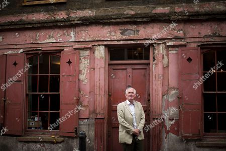 Historian and local resident Dan Cruickshank poses for a portrait outside a Georgian house from the early 18th century on Princelet Street in Spitalfields, where the facade has been kept in a period style so it can be used for location filming purposes in east London. The layering of migrants over centuries, like strata in rock, tells a story vital for Europe to remember as it struggles with new flows of people seeking sanctuary and fresh starts