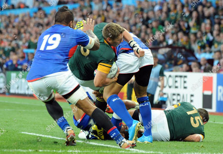South Africa's captain Jean De Villiers is tackled by the Samoa defence during the Rugby World Cup Pool B match between South Africa and Samoa at Villa Park, Birmingham, England