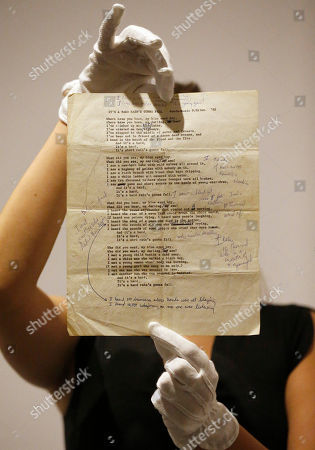"A Sotheby's employee holds up the typed and handwritten lyrics to the song ""It's A Hard Rain's Gonna Fall"" by Bob Dylan, at Sotheby's auction house in London, . Some 650 works from 'Rock & Pop"" are on display ahead of an auction to be held on September 29th. The auction includes works and pieces from The Beatles, Bob Dylan, Bruce Springsteen, David Bowie, Eric Clapton, Jack Bruce, Jimi Hendrix, John Lennon, Led Zeppelin, Oasis, Pink Floyd, The Rolling Stones & The Sex Pistols"