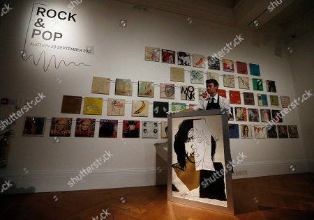 "A Sotheby's employee holds Andy Warhol's portrait of Mick Jagger at Sotheby's auction house in London, . Some 650 works from 'Rock & Pop"" are on display ahead of an auction to be held on September 29th. The auction includes works and pieces from The Beatles, Bob Dylan, Bruce Springsteen, David Bowie, Eric Clapton, Jack Bruce, Jimi Hendrix, John Lennon, Led Zeppelin, Oasis, Pink Floyd, The Rolling Stones & The Sex Pistols"