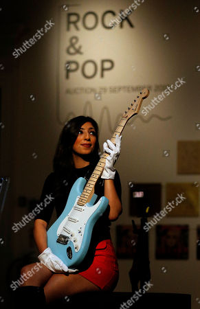 "A Sotheby's employee poses for a photograph with a Fender Stratocaster guitar that belonged to Eric Clapton, at Sotheby's auction housem London, . Some 650 works from 'Rock & Pop"" are on display ahead of an auction to be held on September 29th. The auction includes works and pieces from The Beatles, Bob Dylan, Bruce Springsteen, David Bowie, Eric Clapton, Jack Bruce, Jimi Hendrix, John Lennon, Led Zeppelin, Oasis, Pink Floyd, The Rolling Stones & The Sex Pistols"