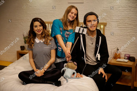 "A youngster, center, poses for photographers at the launch of waxworks of internet video-sharing website YouTube ""vlog"", video blog, British celebrities Zoe Sugg, left, and Alfie Deyes, at Madame Tussauds waxworks in London, . The couple are very popular with youngsters, with their YouTube channels attracting a combined number of over 13 million subscribers"