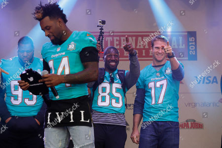 Miami Dolphins quarterback Ryan Tannehill, right, and wide receiver Greg Jennings, 85, point at the crowd beside defensive tackle Ndamukong Suh, left, and wide receiver Jarvis Landry, second left, as they appear on stage during an NFL fan rally in Trafalgar Square, in London, . The Miami Dolphins are playing the New York Jets in an NFL football game at London's Wembley stadium on Sunday