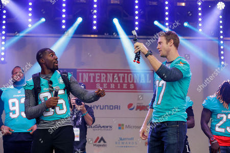 Miami Dolphins quarterback Ryan Tannehill, right, films his teammate wide receiver Greg Jennings, backdropped by defensive tackle Ndamukong Suh, left, on stage during an NFL fan rally in Trafalgar Square, in London, . The Miami Dolphins are playing the New York Jets in an NFL football game at London's Wembley stadium on Sunday