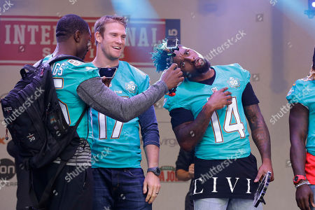 Miami Dolphins wide receiver Greg Jennings, left, films wide receiver Jarvis Landry, right, beside quarterback Ryan Tannehill as they appear on stage during an NFL fan rally in Trafalgar Square, in London, . The Miami Dolphins are playing the New York Jets in an NFL football game at London's Wembley stadium on Sunday