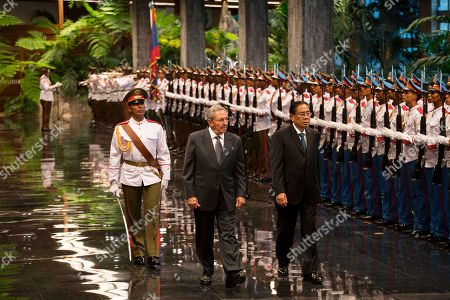 Cuba's President Raul Castro, left center, and President of Laos Choummaly Sayasone, review troops during a welcoming ceremony at Revolution Palace in Havana, Cuba