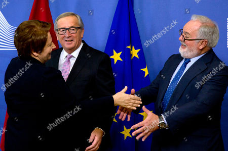 European Commission President Jean-Claude Juncker, center, and European Commissioner for Energy Miguel Arias Canete, right, greet Latvian Prime Minister Laimdota Straujuma prior to the signing of a gas pipeline agreement at EU headquarters in Brussels on