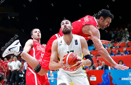 Lithuania's Jonas Valanciunas, center, looks up at a basket while Georgia's Zaza Pachulia falls over during the EuroBasket European Basketball Championship match, round of sixteen, between Lithuania against Georgia, at Pierre Mauroy stadium in Lille, northern France