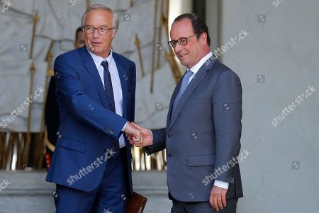 Outgoing Labor minister Francois Rebsamen, left, shakes hands with French President Francois Hollande, at the end of the weekly cabinet meeting at the Elysee Palace, in Paris, France