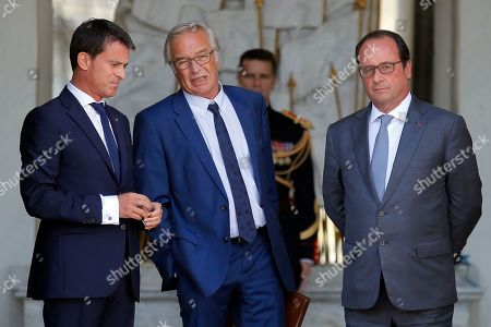 Outgoing Labor minister Francois Rebsamen, center, stands between French Prime Minister Manuel Valls, left, and French President Francois Hollande, at the end of the weekly cabinet meeting at the Elysee Palace, in Paris, France