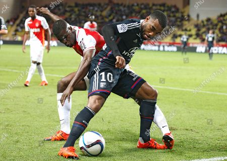 Lyon's Alexandre Lacazette, right, challenges for the ball with Monaco's Elderson Uwa Echiejile during their French League One soccer match, in Monaco stadium